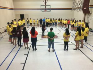 Summer camp students standing in a circle in the gym
